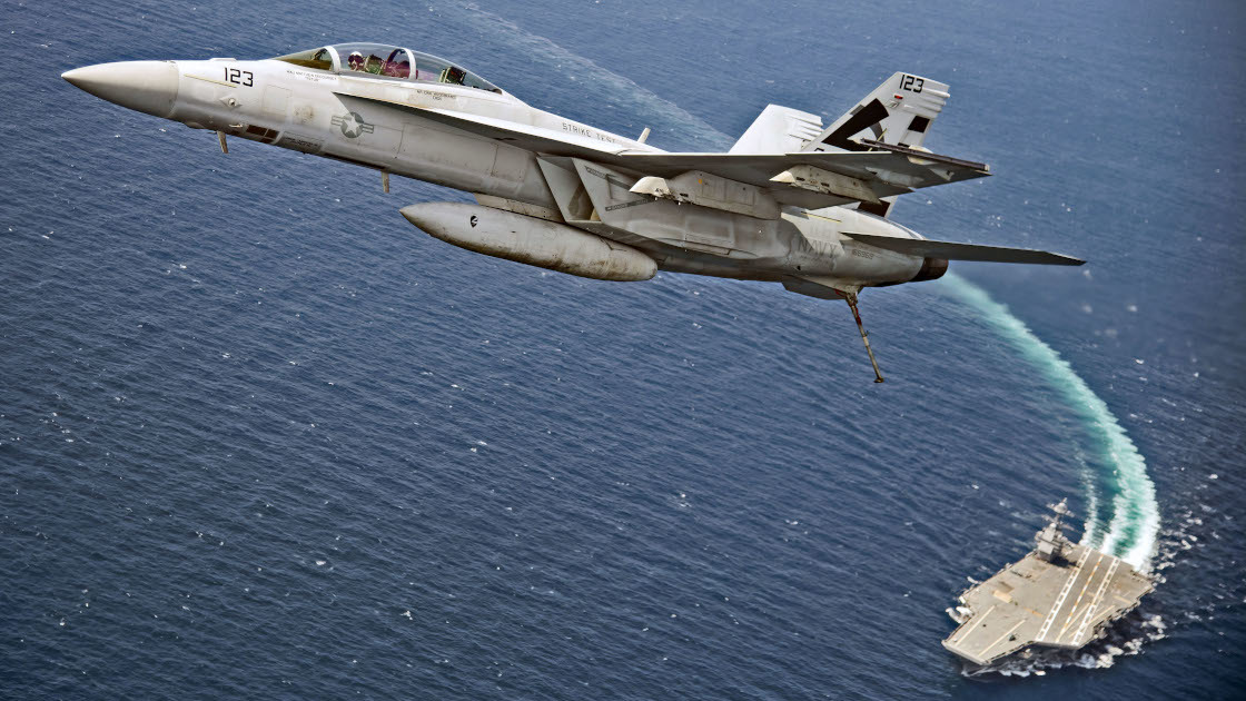 An F/A-18F Super Hornet flies over  USS Gerald R. Ford via [navy.mil](https://www.navy.mil/submit/display.asp?story_id=101711)