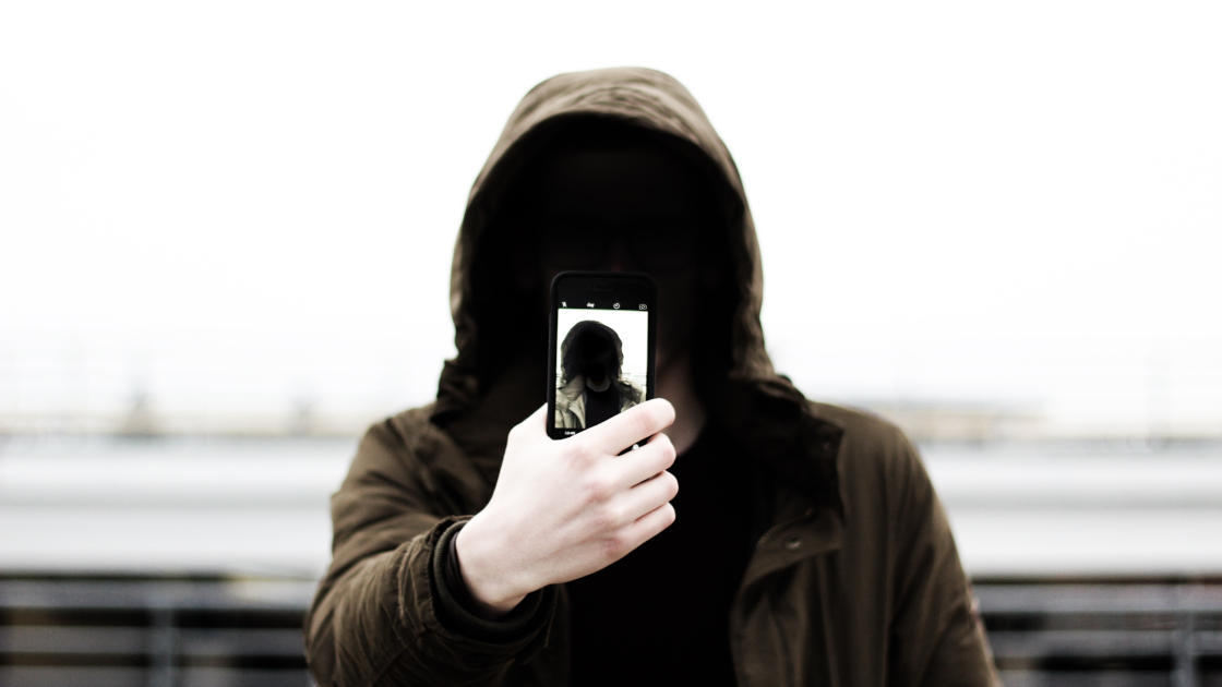 Shady guy with smartphone and a hoodie